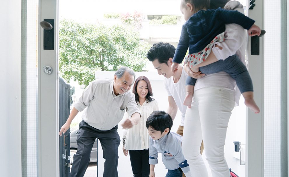 Young family welcoming grandparents at home